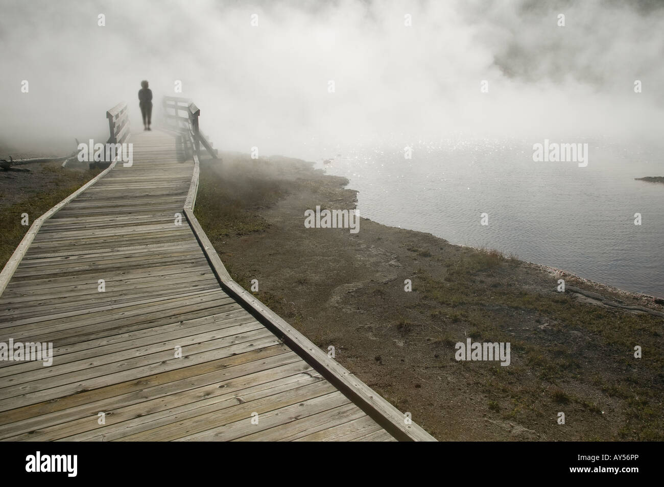 smoke or fog surrounds someone strolling down a sidewalk - Stock Image