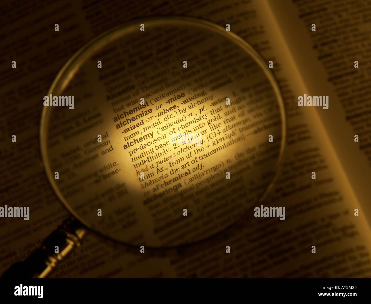 MAGNIFYING GLASS ON DICTIONARY PAGE SHOWING DEFINITION OF THE WORD ALCHEMY - Stock Image