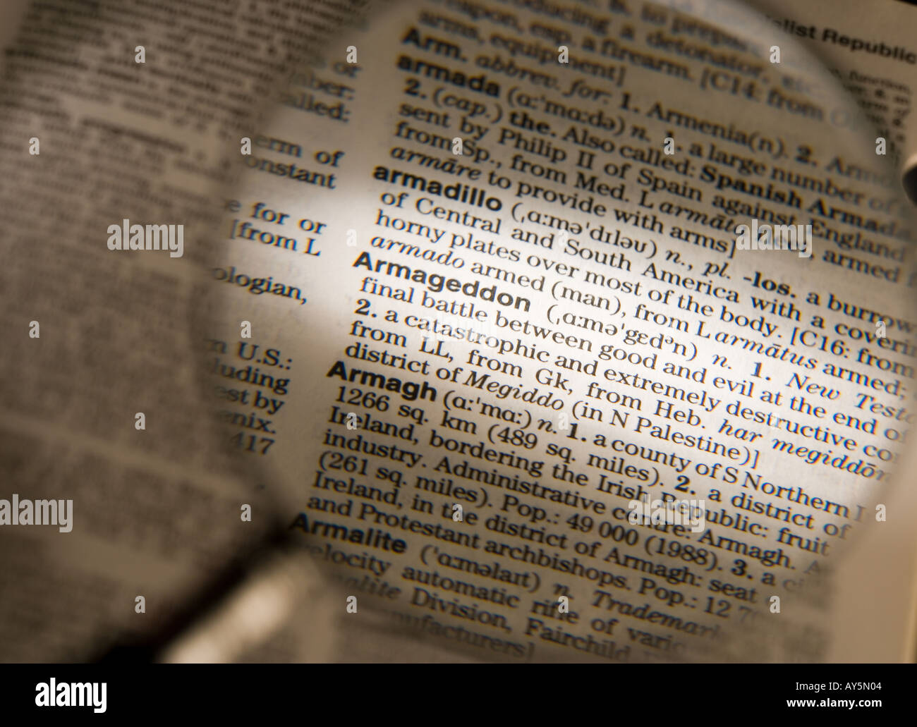 MAGNIFYING GLASS ON DICTIONARY PAGE SHOWING DEFINITION OF THE WORD ARMAGEDDON - Stock Image