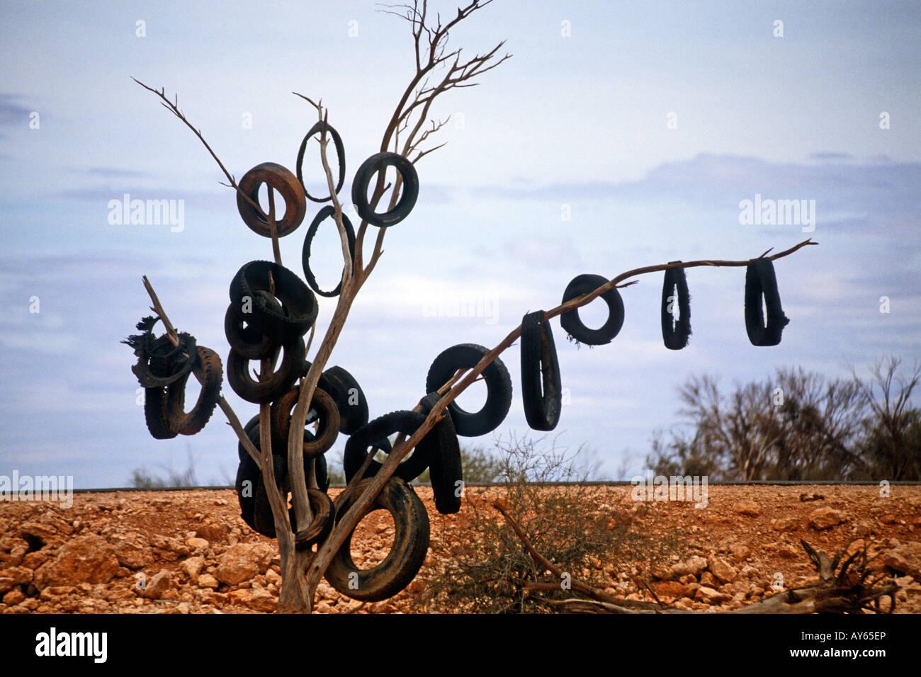 Australia Near Alice Springs Old tyres adorn a tree - Stock Image