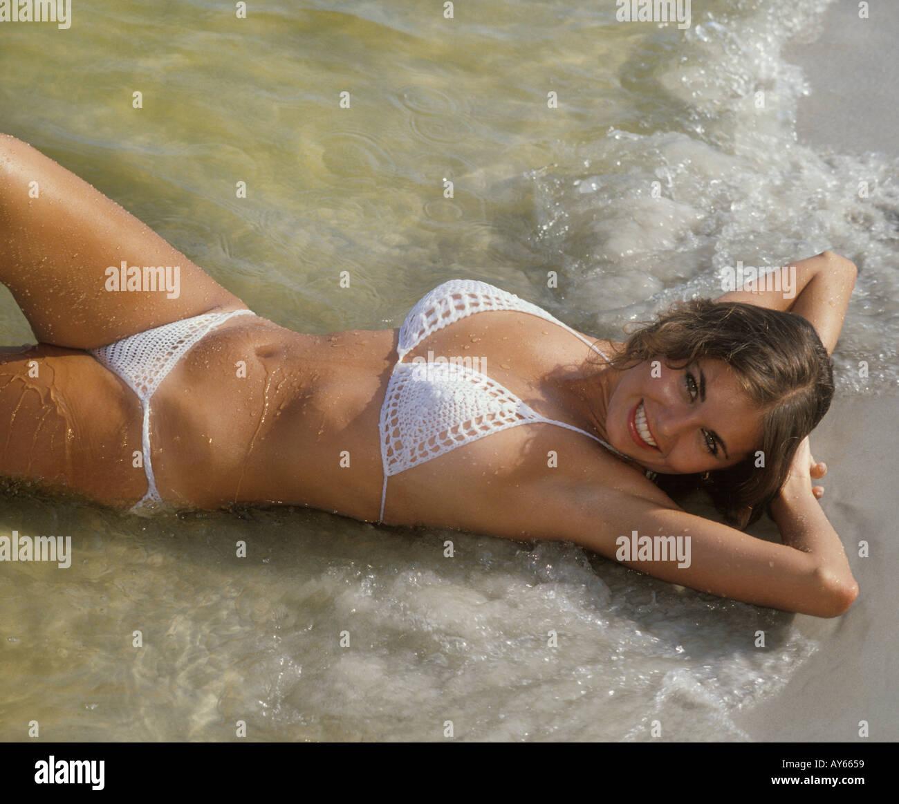pretty girl in bikini lying in surf at beach - Stock Image