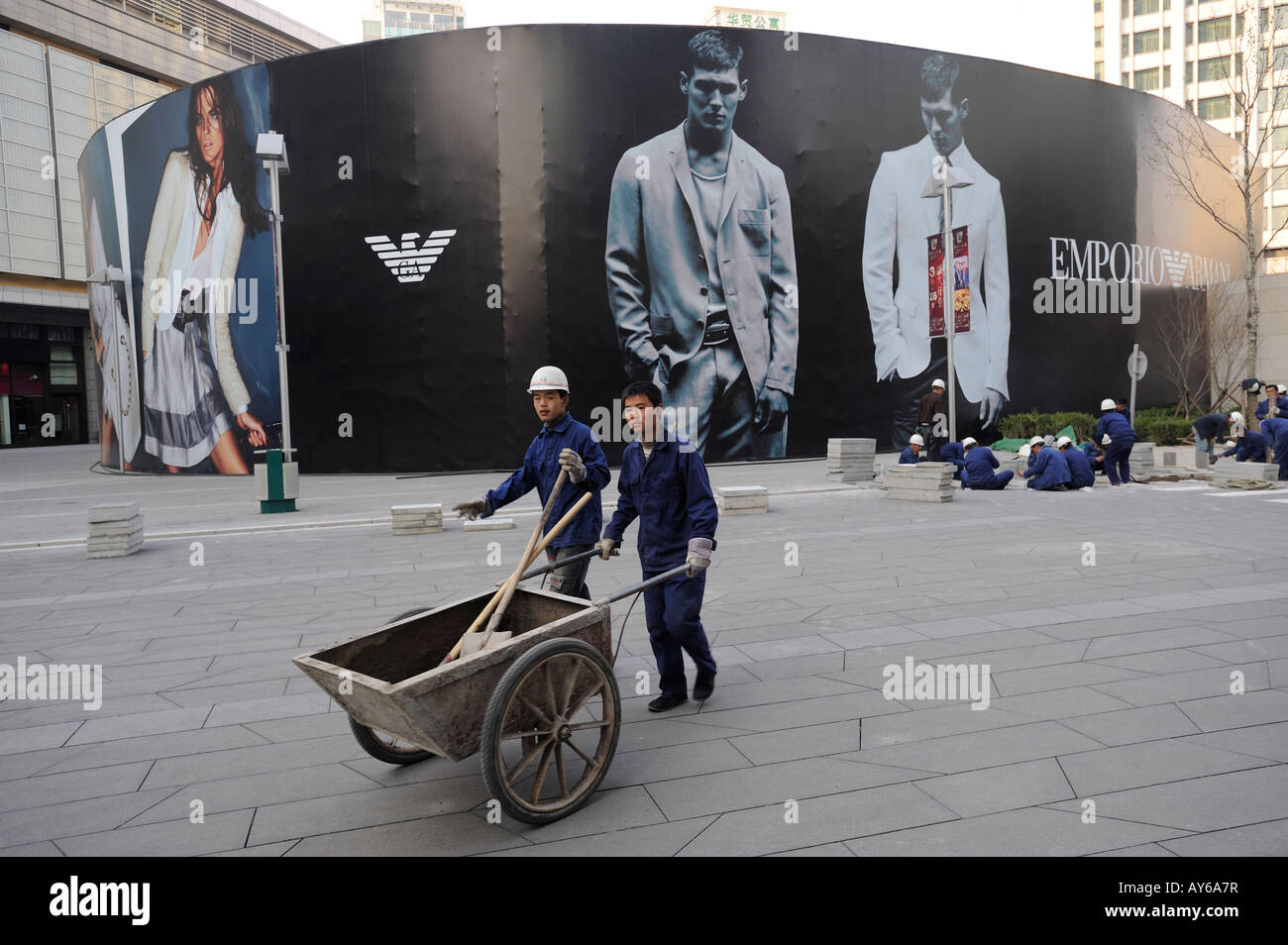 Chinese workers pave tiles in front of a huge billboard of Emporio Armani in Beijing CBD, China. 03-Apr-2008 - Stock Image