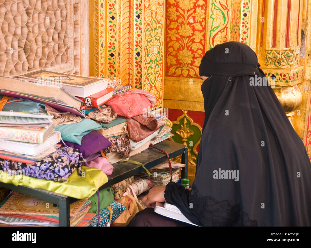 A woman reading from the Koran at a mosque - Stock Image