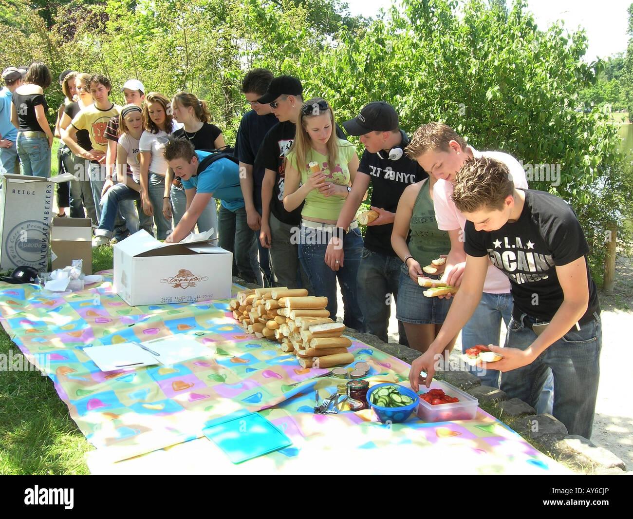 Group of schoolchildren enjoying picnic in Bois de Boulogne Paris France - Stock Image