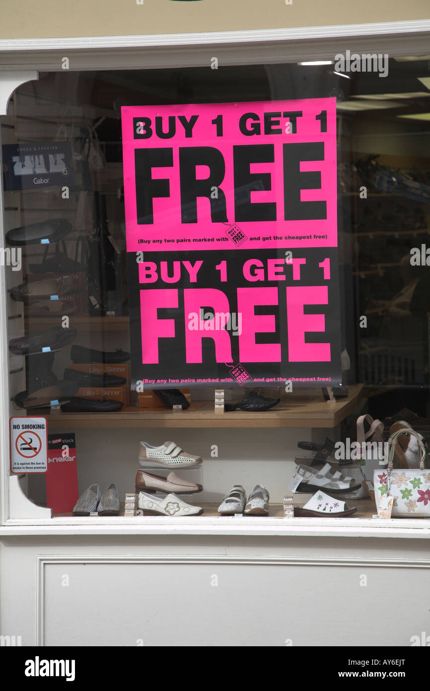 Buy One Get one free offer sign in display window of shoe shop Stock