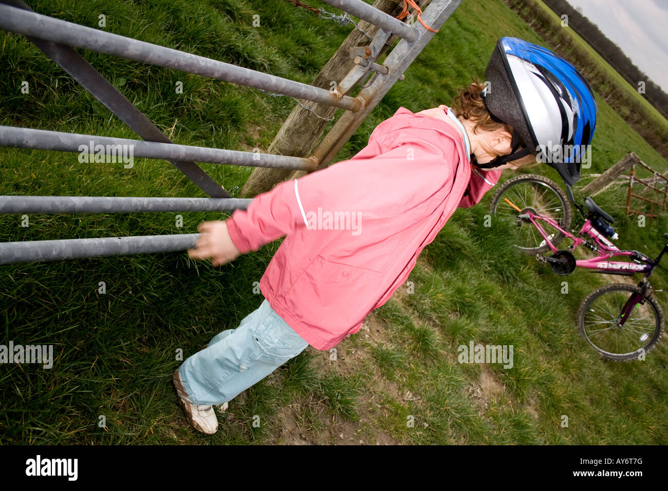 young girl with bike in field - Stock Image
