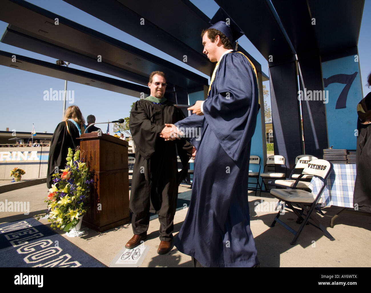 High school senior shakes hands with teacher during commencement - Stock Image