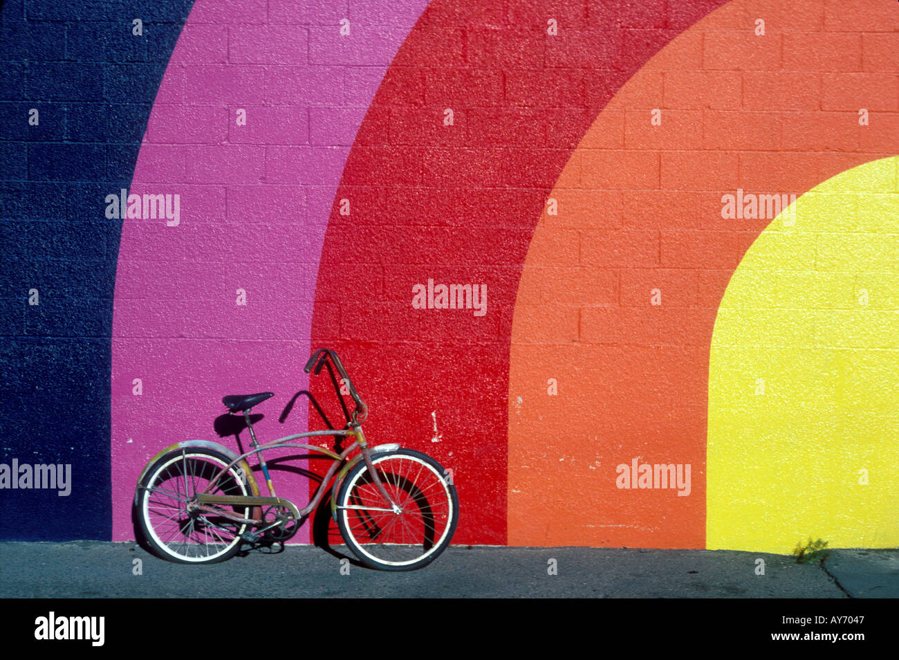 Old bike leaning against rainbow colored wall - Stock Image