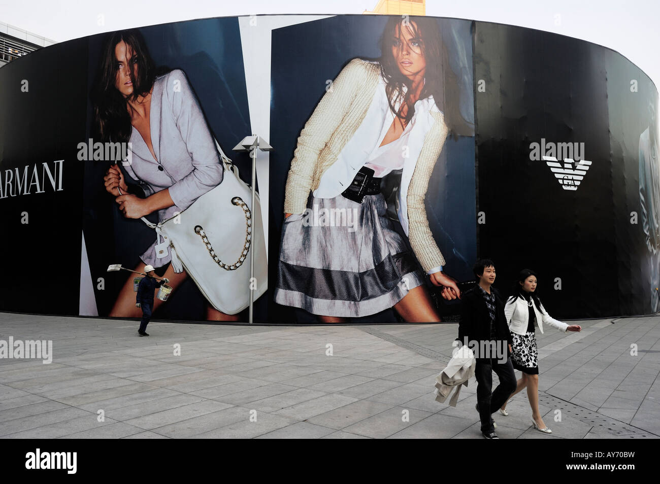 People walk past a huge billboard of Emporio Armani in Beijing CBD, China. 03-Apr-2008 - Stock Image