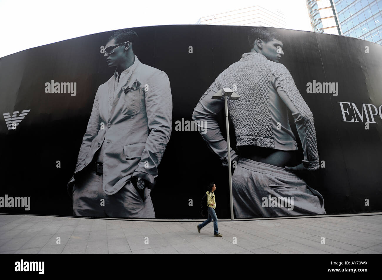 A migrant worker walks past a huge billboard of Emporio Armani in Beijing CBD, China. 03-Apr-2008 - Stock Image