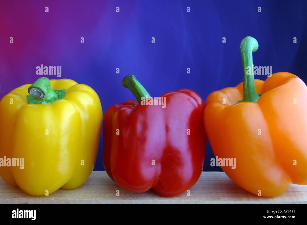 Yellow red and orange bell peppers with purple background - Stock Image