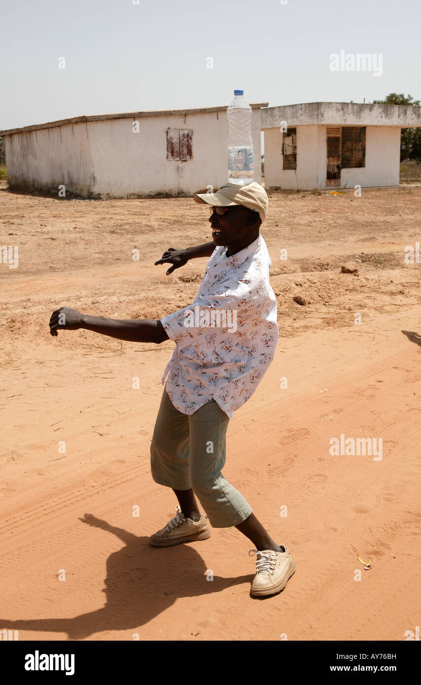 African man with water bottle on head The Gambia West Africa - Stock Image