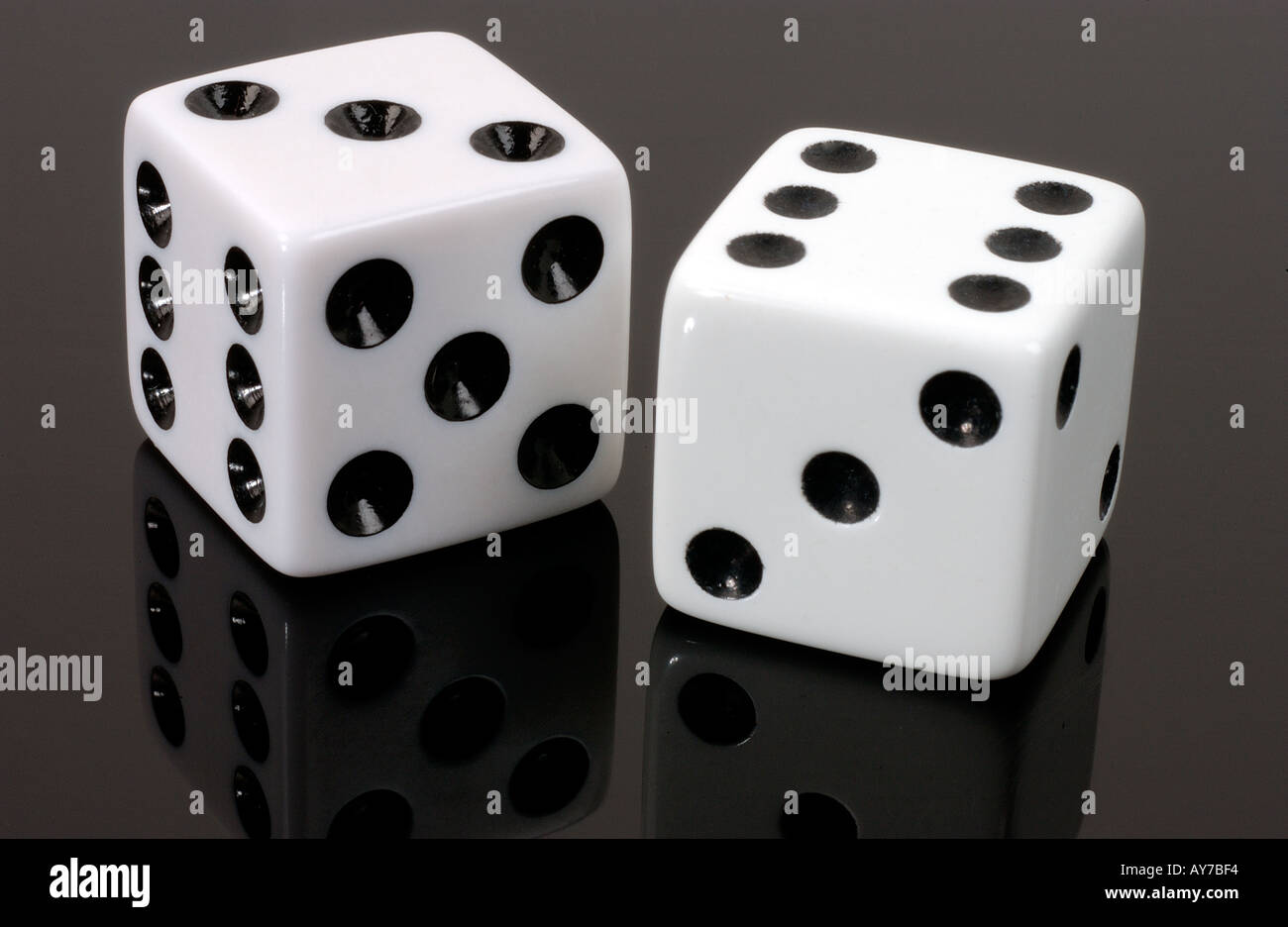 a pair of white dice on black acrylic - Stock Image