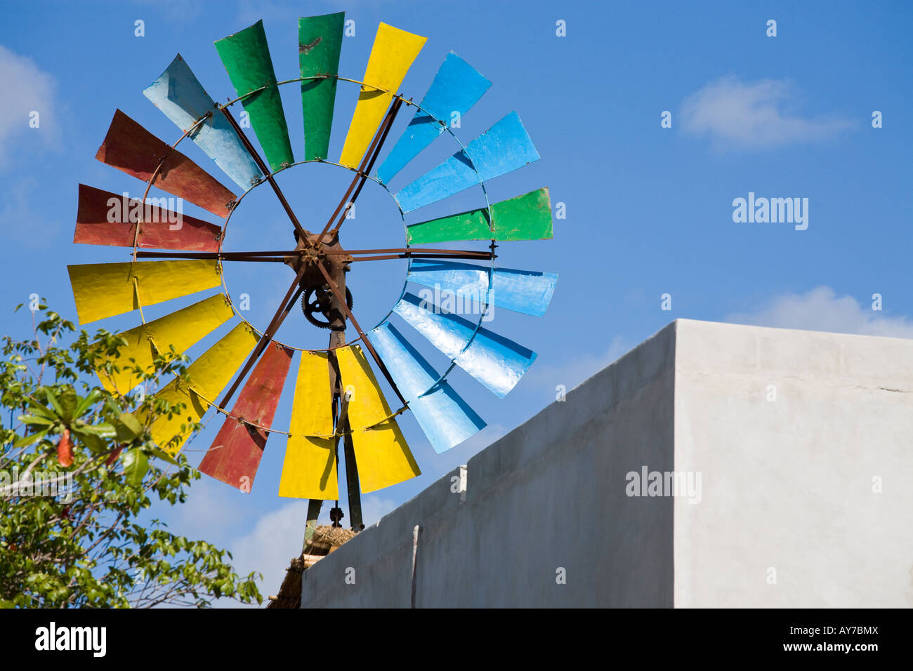 Painted Windmill An old rusted windmill rises above a plain building The vanes brightly painted different colours - Stock Image
