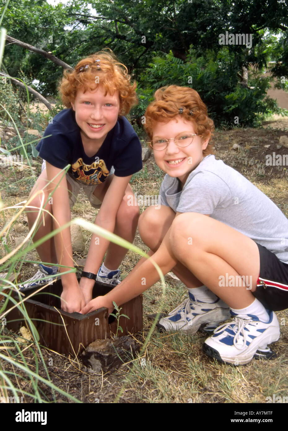 Two cute red-headed sisters wash up, at Fine Art Days in Lincoln, New Mexico. - Stock Image