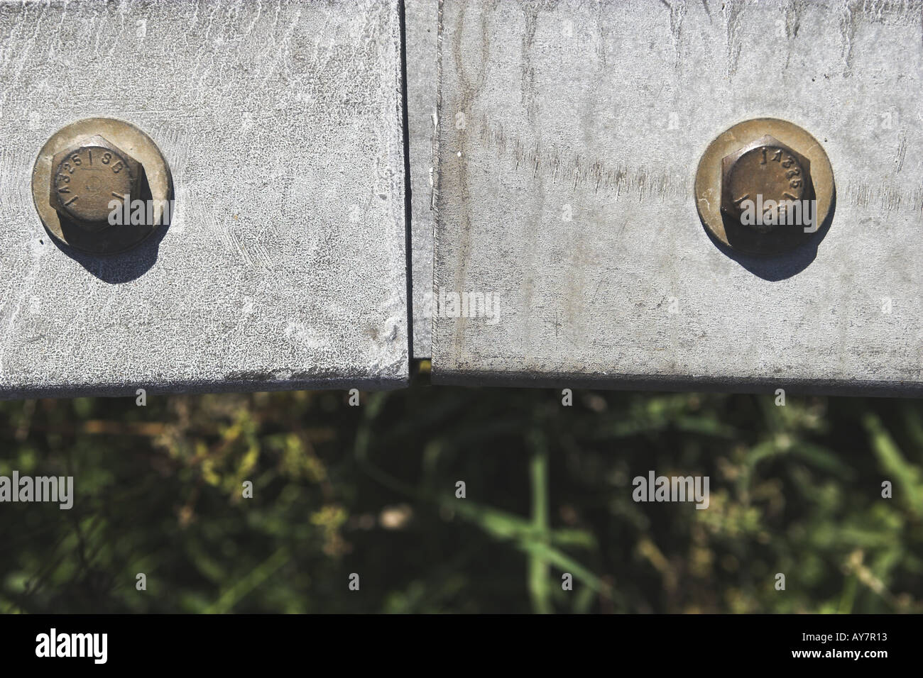 Close up of steel guard railing and two bolt heads securing - Stock Image
