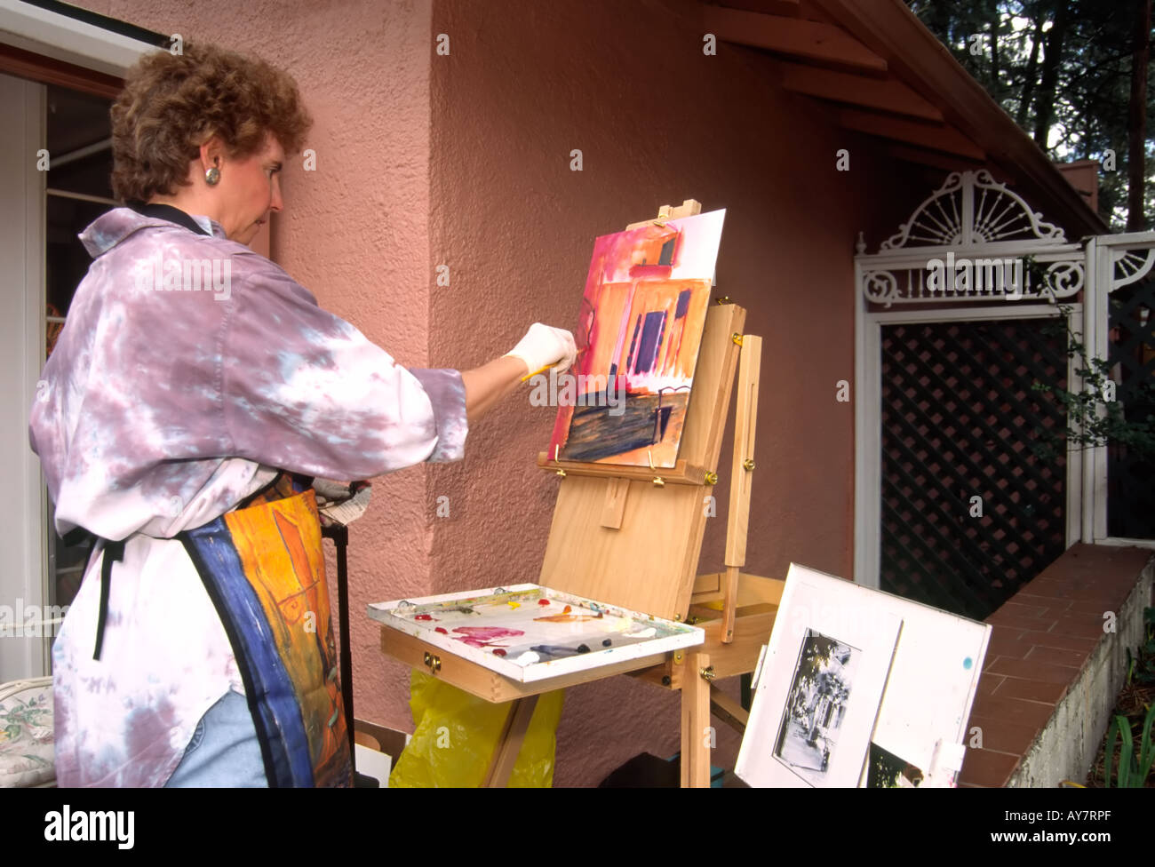 A local artist demonstrates her painting technique, at the Street Players Festival in downtown Ruidoso, New Mexico. Stock Photo