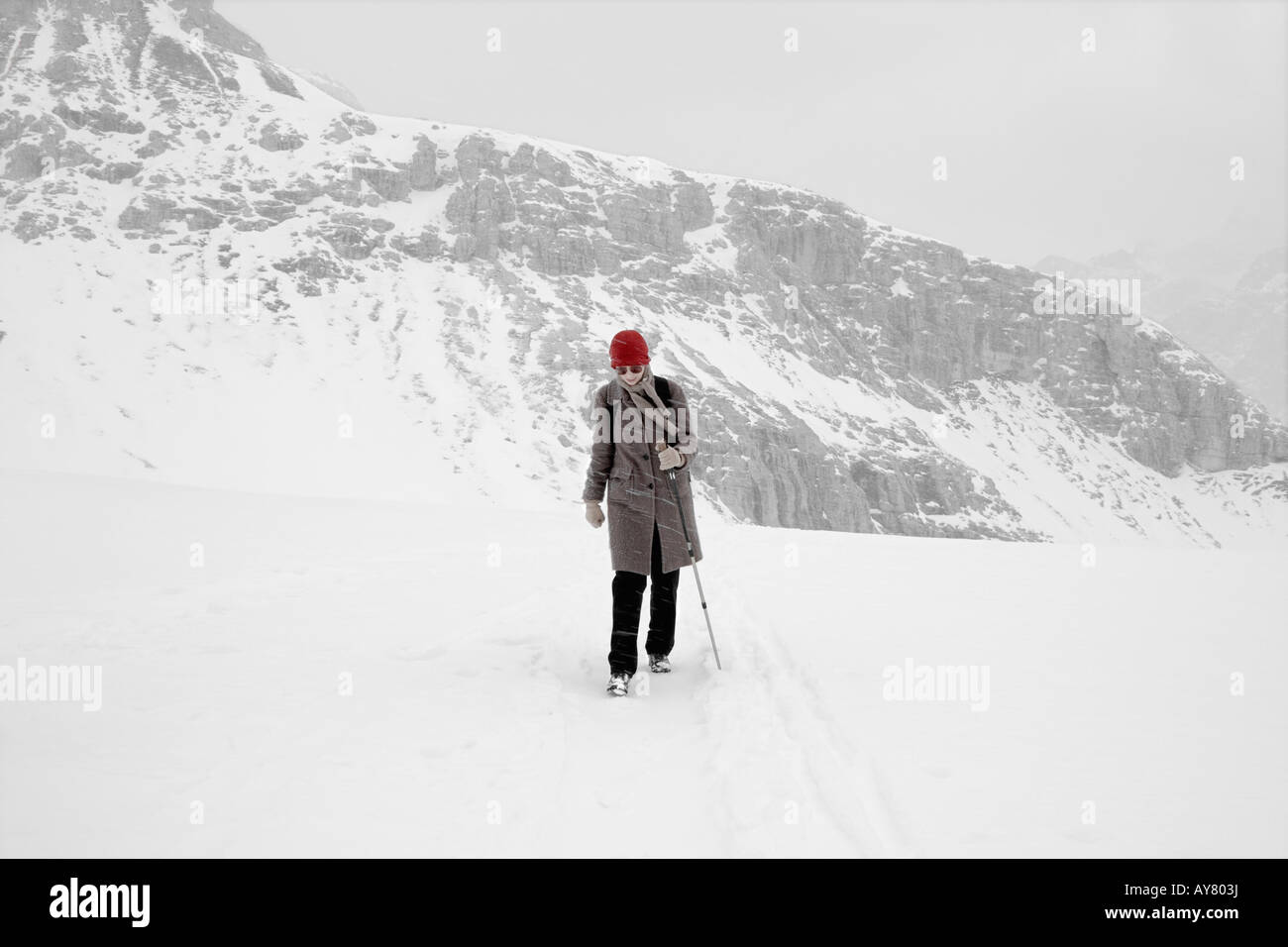 One Young Woman Crossing Mountain Top In Snowstorm - Stock Image