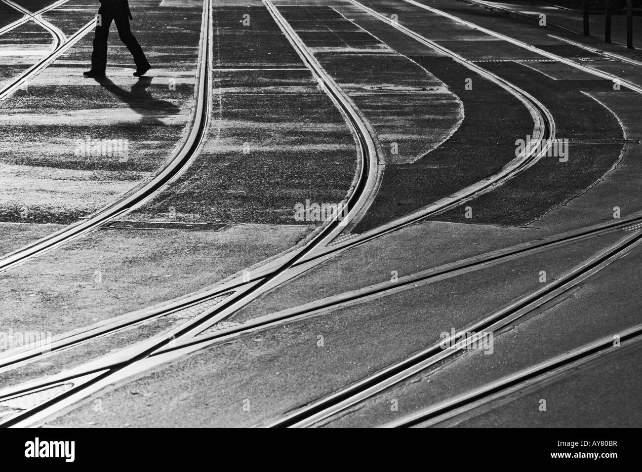 One Person Walking Across Streetcar Tracks - Stock Image