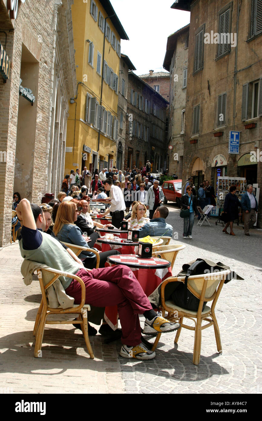 people enjoying sunshine at a street cafe in Urbino Le Marche, the Marches, Italy Stock Photo