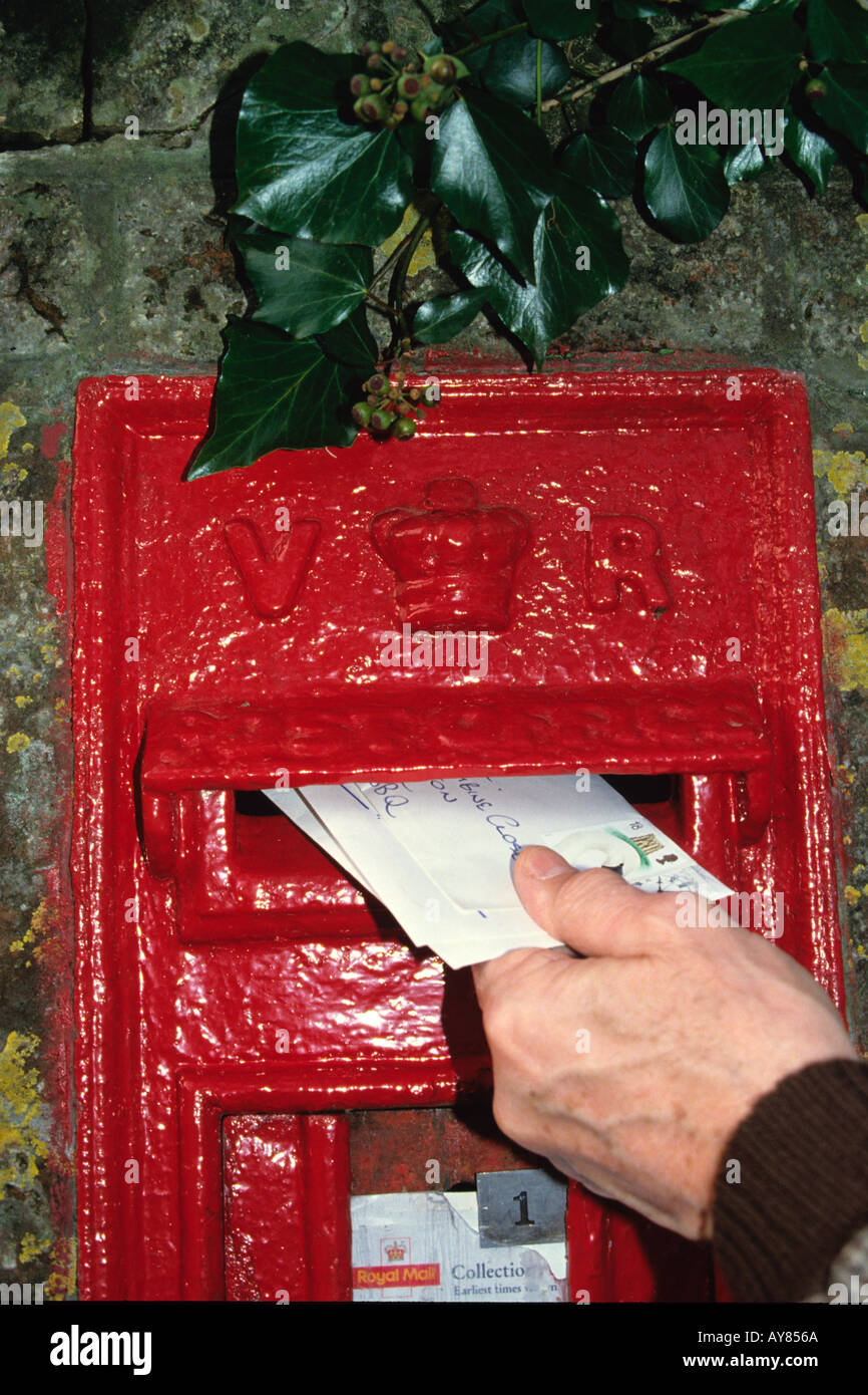 hand posting a letter in red British postbox - Stock Image