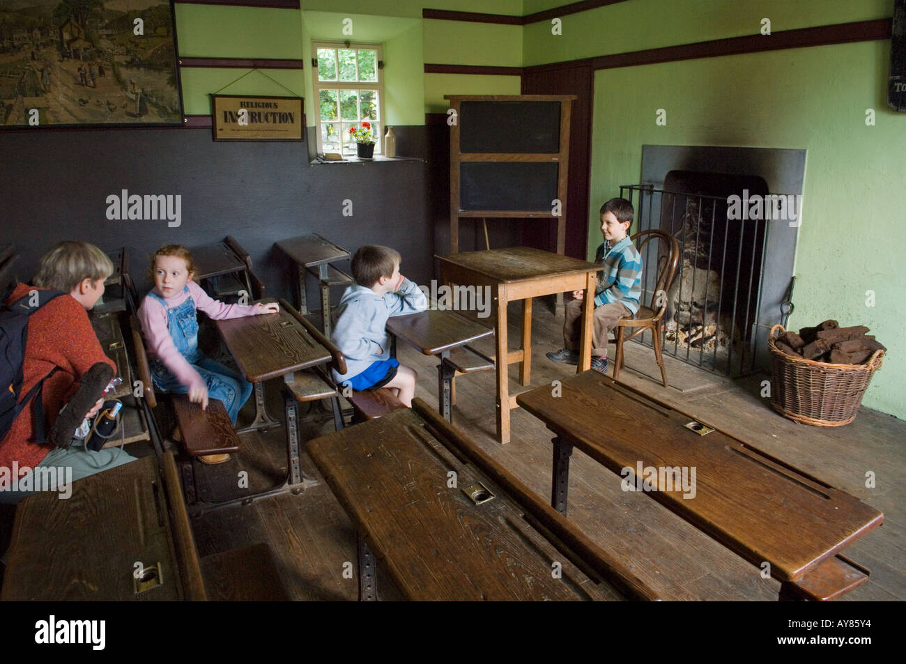 Bunratty Folk Park, Bunratty Castle, Co. Clare, Ireland. Children pupils and mother teacher explore the School House Stock Photo
