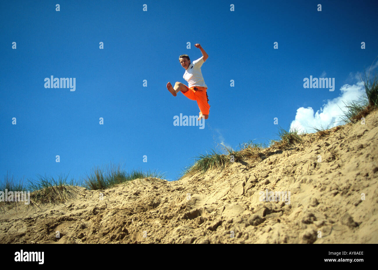 Boy jumping sand dunes Camber Sands beach Sussex England South Coast UK Site of Special Scientific Interest SSSI RAMSAR SNCI - Stock Image