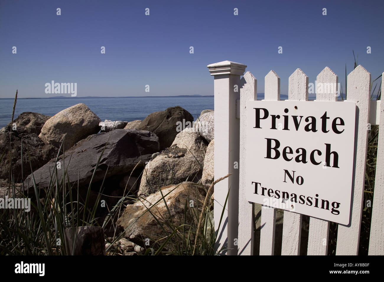 Private beach sign and white picket fence on west shore Whidbey Island Washington - Stock Image