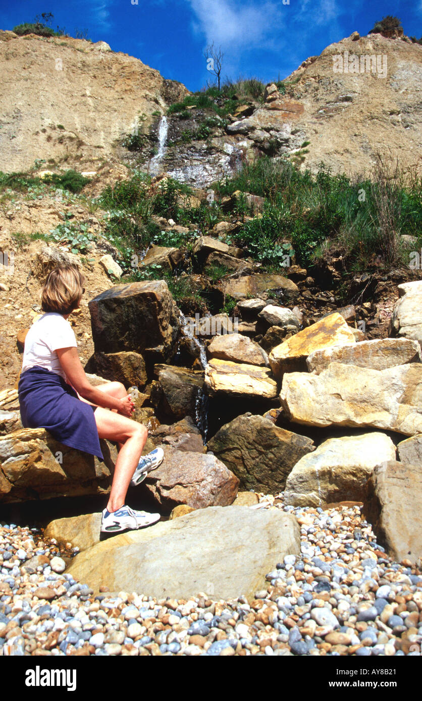 Woman looking at a waterfall on the beach in Hastings Country Park Hastings East Sussex England South Coast BritainUK Stock Photo