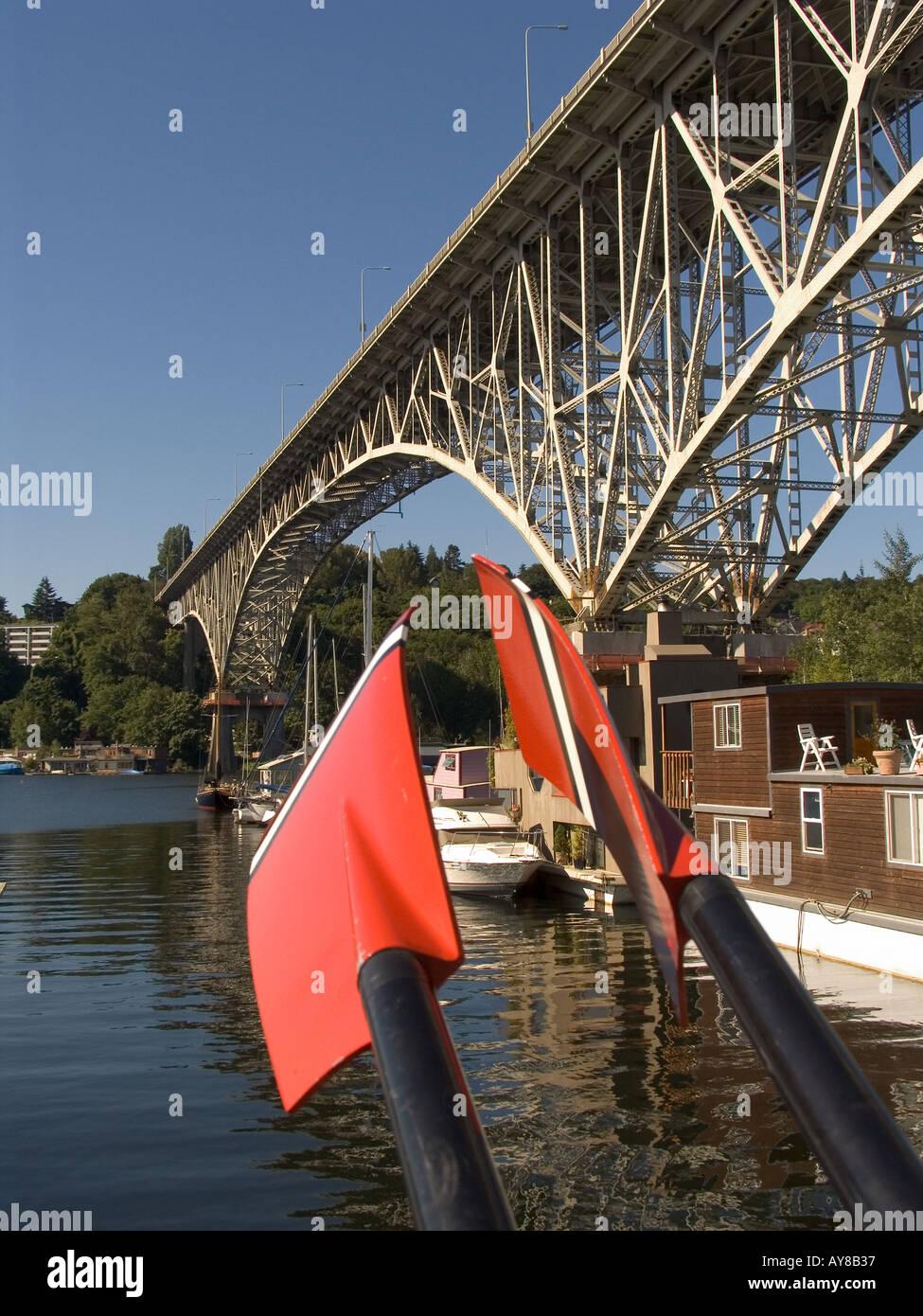 Red tipped skulling oars Aurora Bridge marina with sailboat and houseboat moorage on north shore of Lake Union Seattle Washi - Stock Image