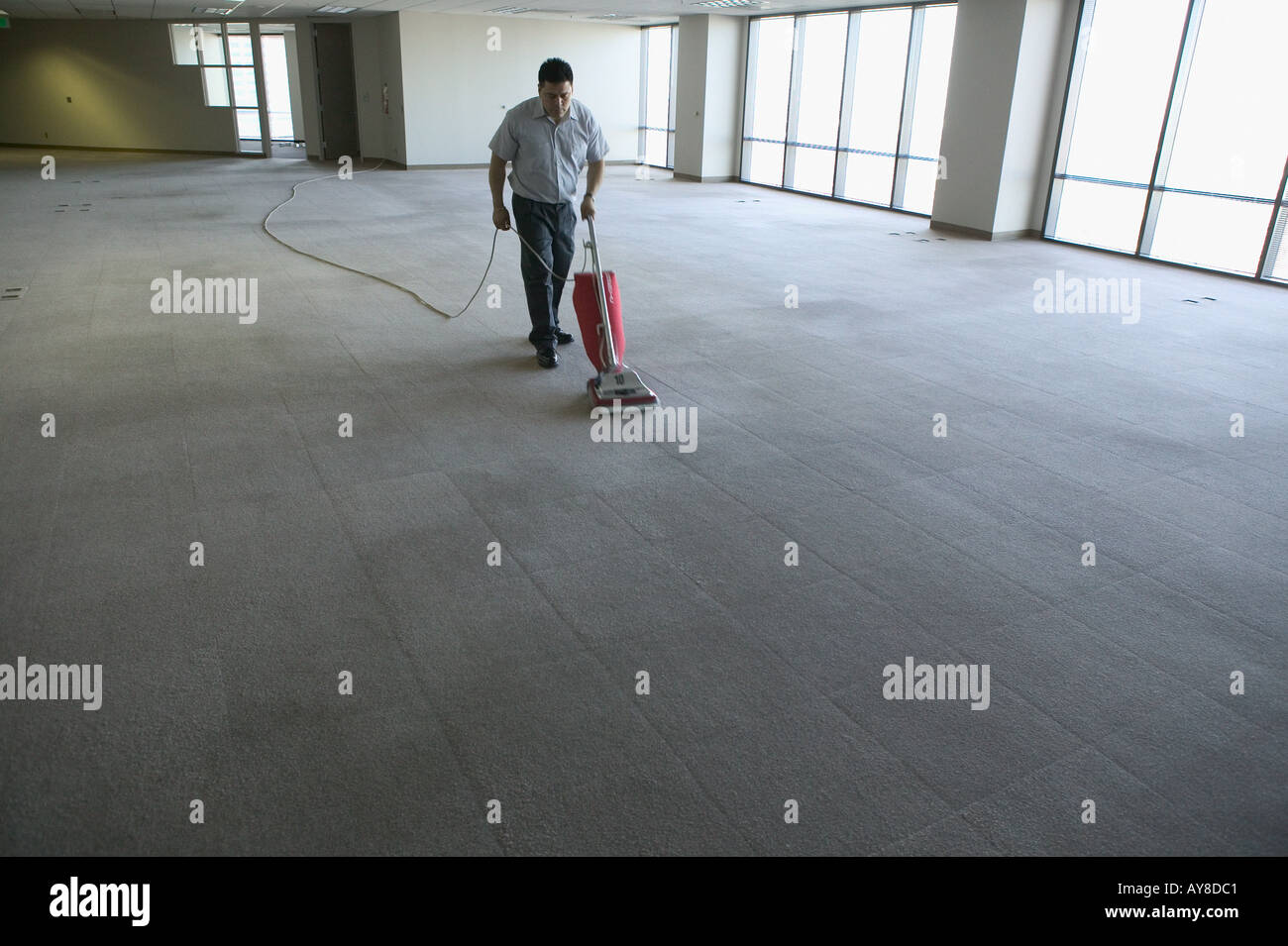 Vacant office building is being vacuumed by janitor after company moved out or about to move in - Stock Image