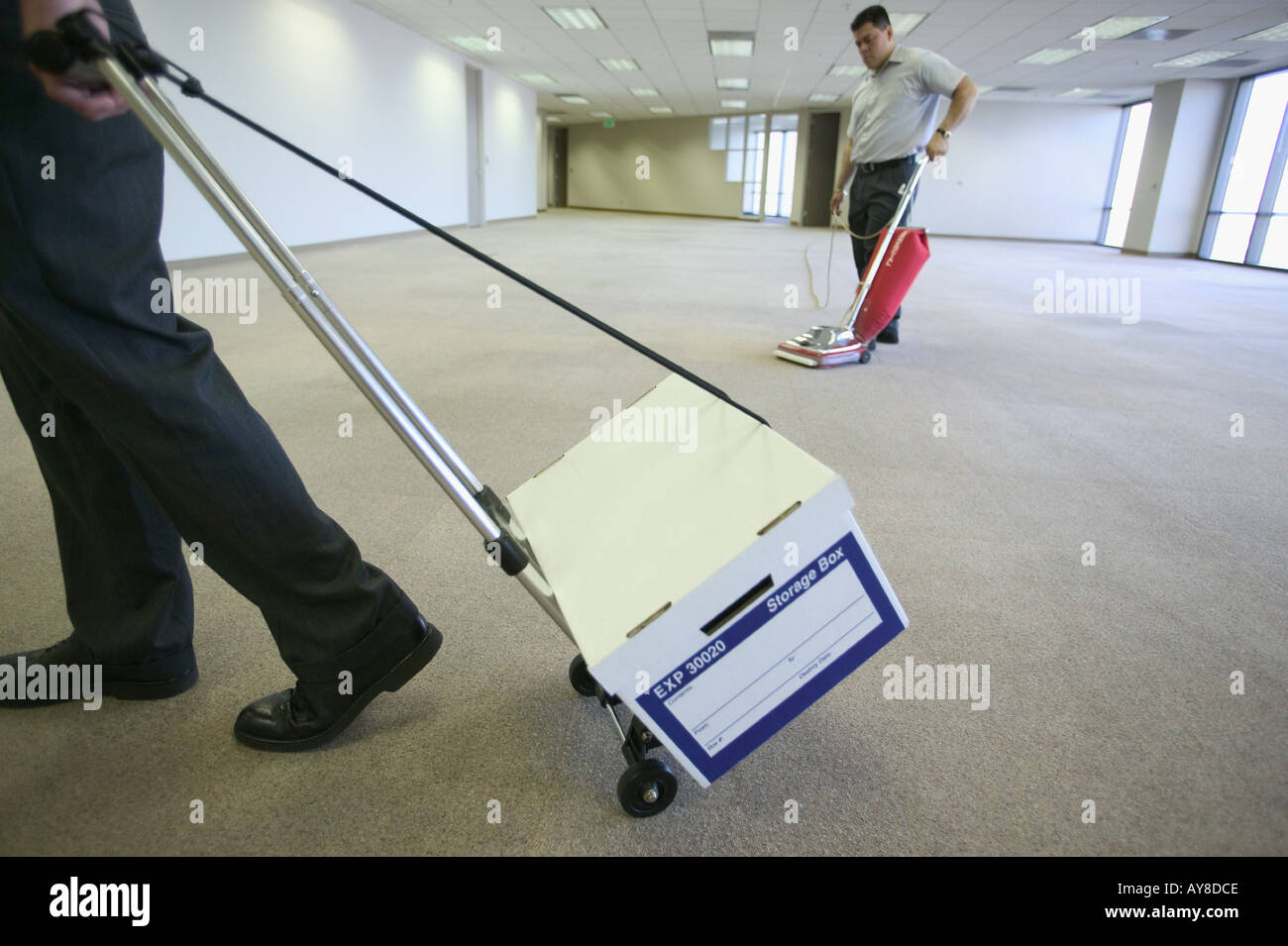 Young office worker moving into or moving out of vacant office space in hi rise office building while janitor vacummes - Stock Image