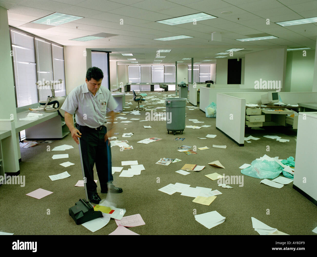 Janitor sweeps up paperwork mess after employees are gone from highrise office Stock Photo