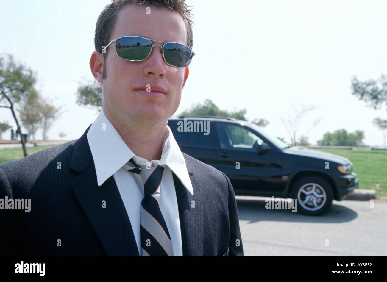 Young Professional With Coat And Tie And BMW Car
