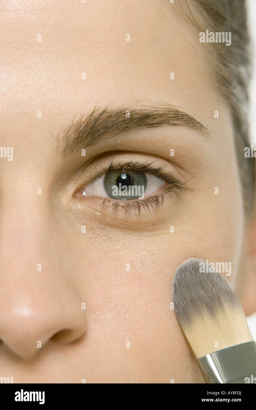 Woman applying make-up to cheek, cropped view of face - Stock Image