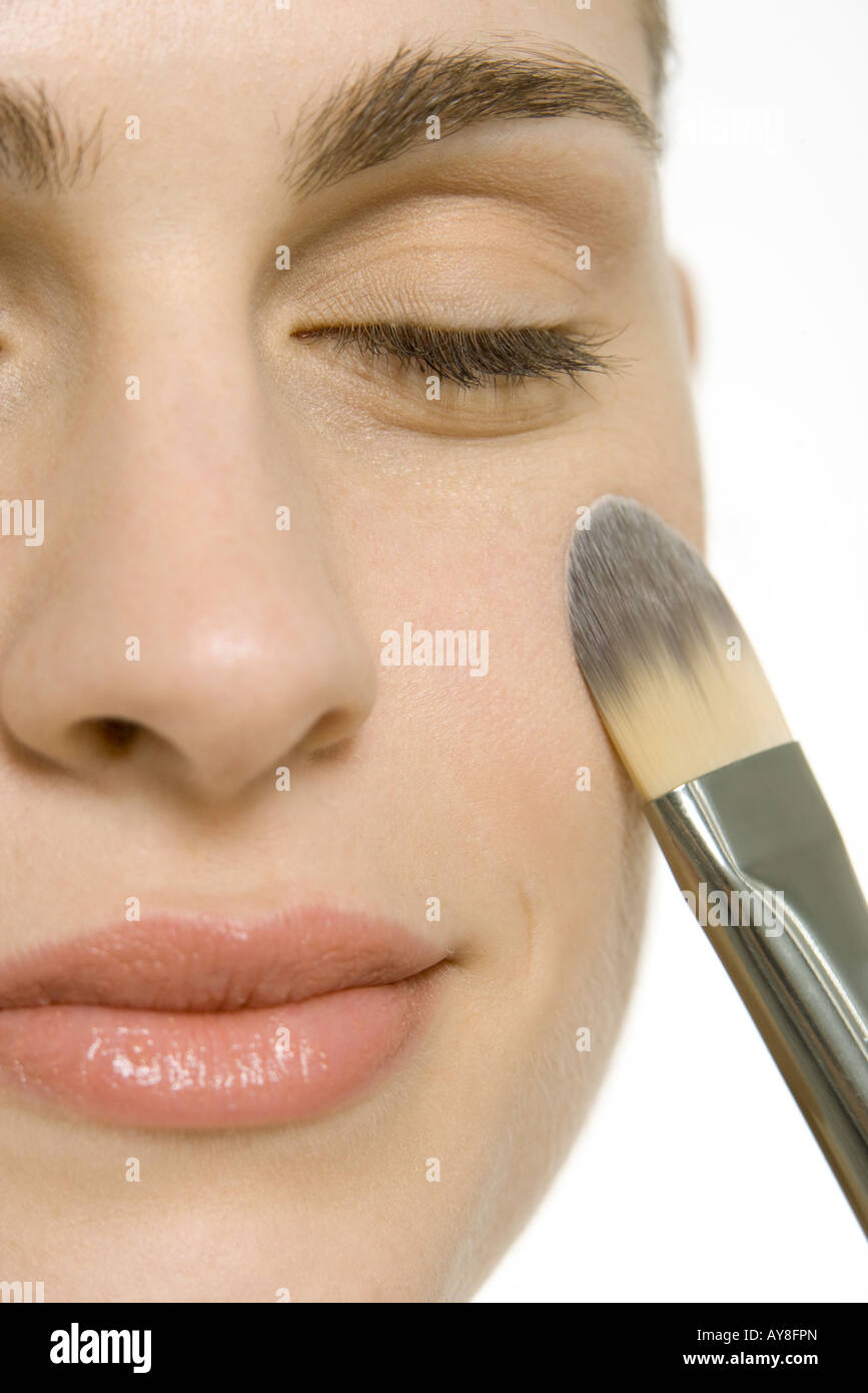 Woman putting on blush, smiling with eyes closed, close-up of face - Stock Image