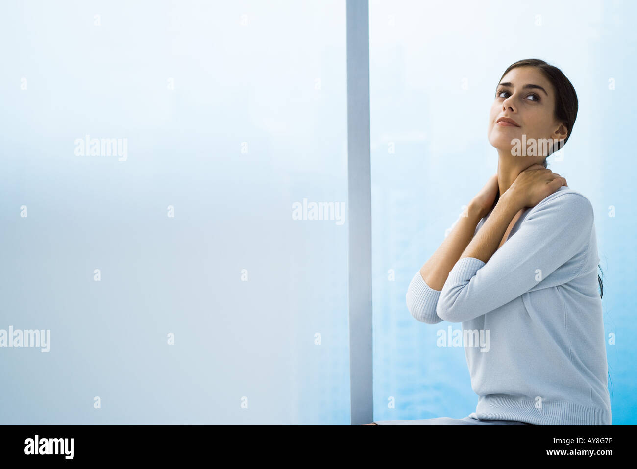 Woman with hands behind neck, looking up - Stock Image