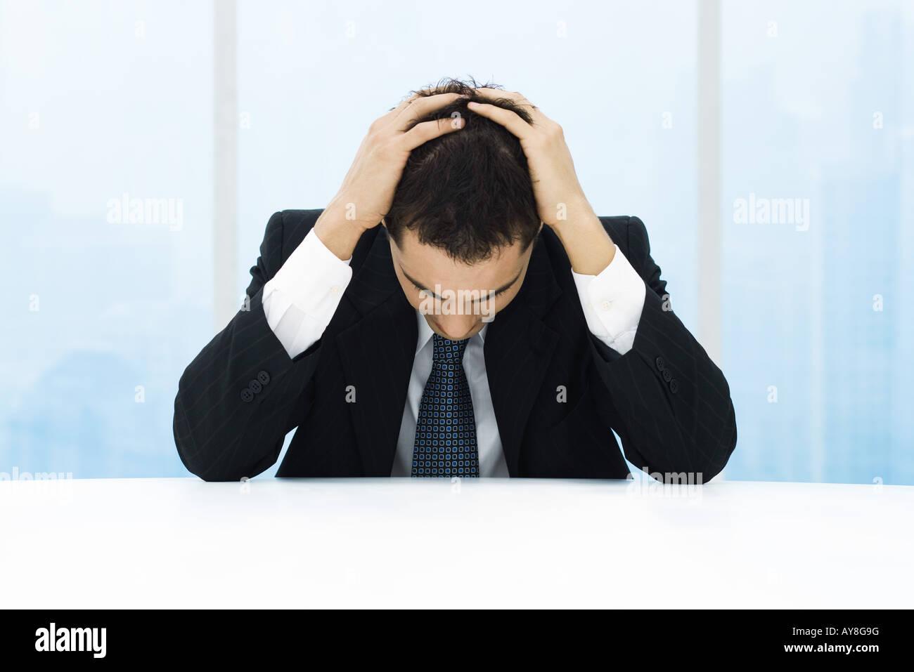Businessman holding head - Stock Image