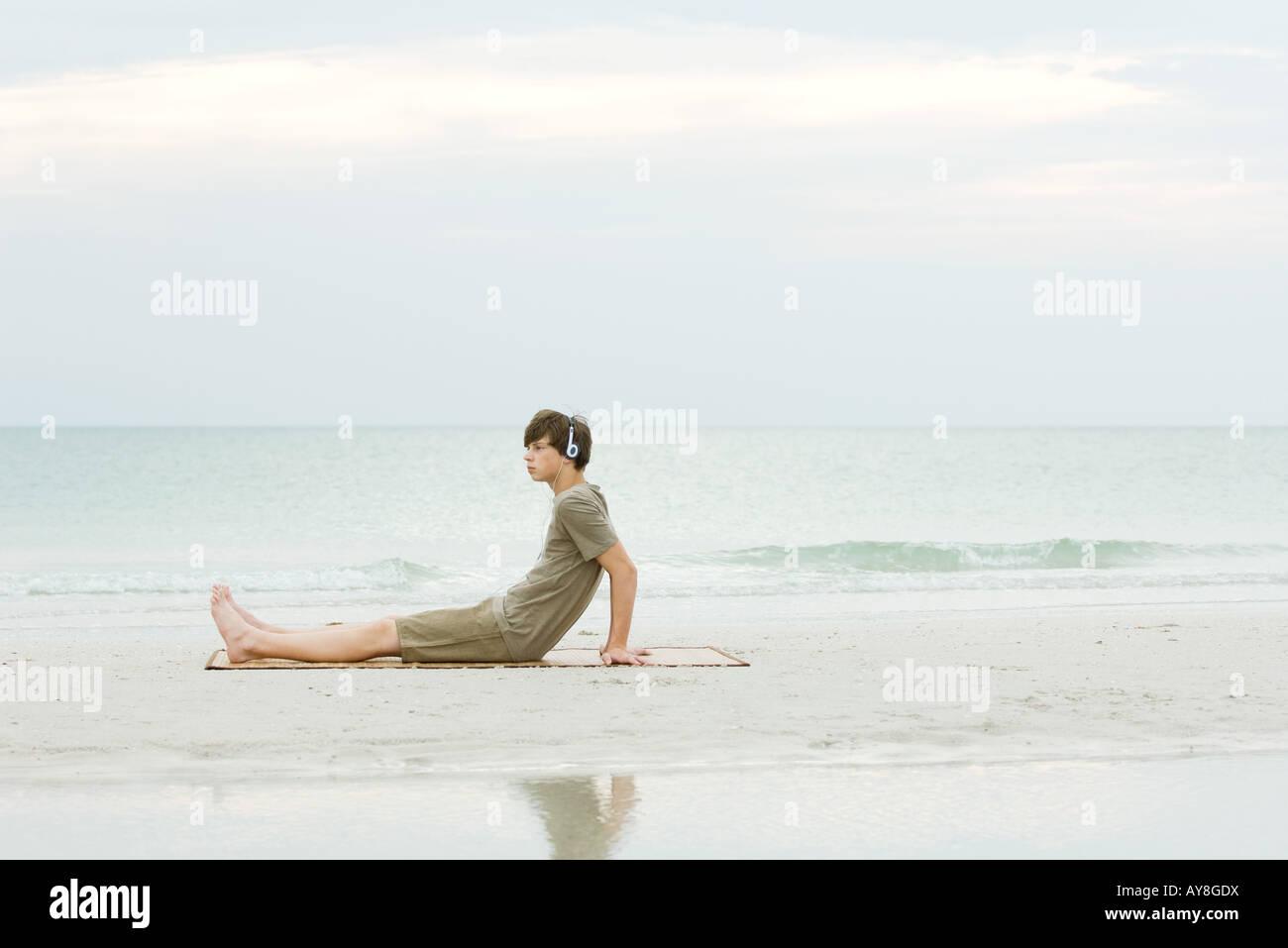 Teenage boy sitting on the beach, listening to headphones, side view Stock Photo