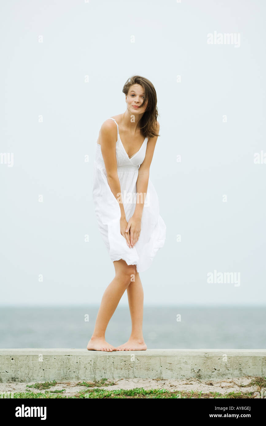 Teenage girl in front of the sea, bending over to hold skirt, tousled by wind, smiling at camera - Stock Image
