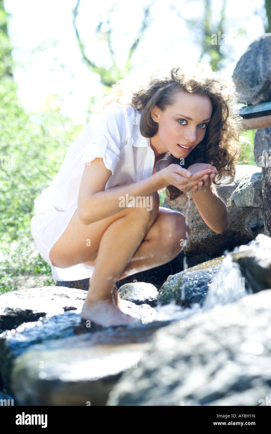 Young woman crouching on rocks, holding water in cupped hands, looking at camera - Stock Image