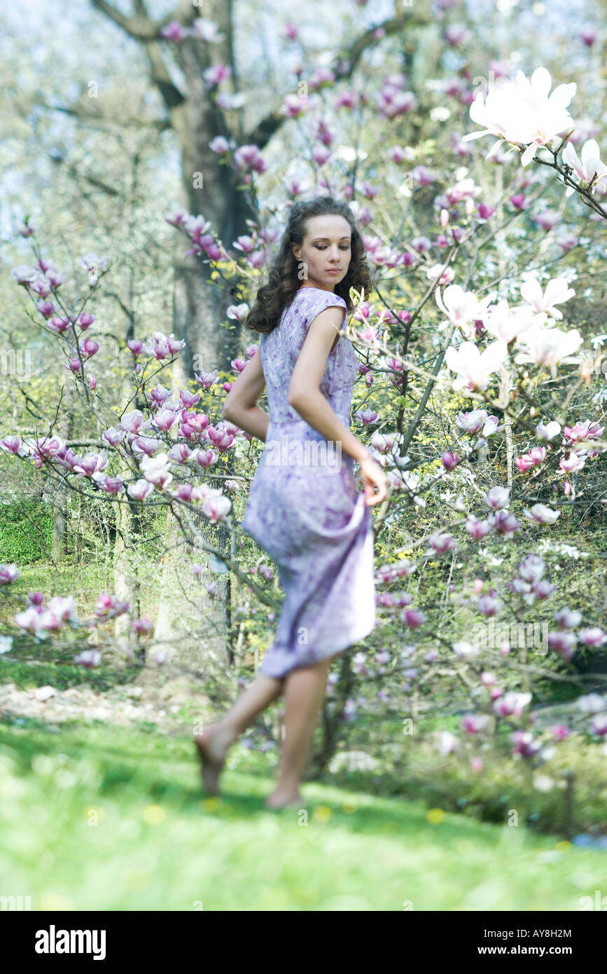 Young woman in dress walking in meadow, looking over shoulder, low angle view - Stock Image