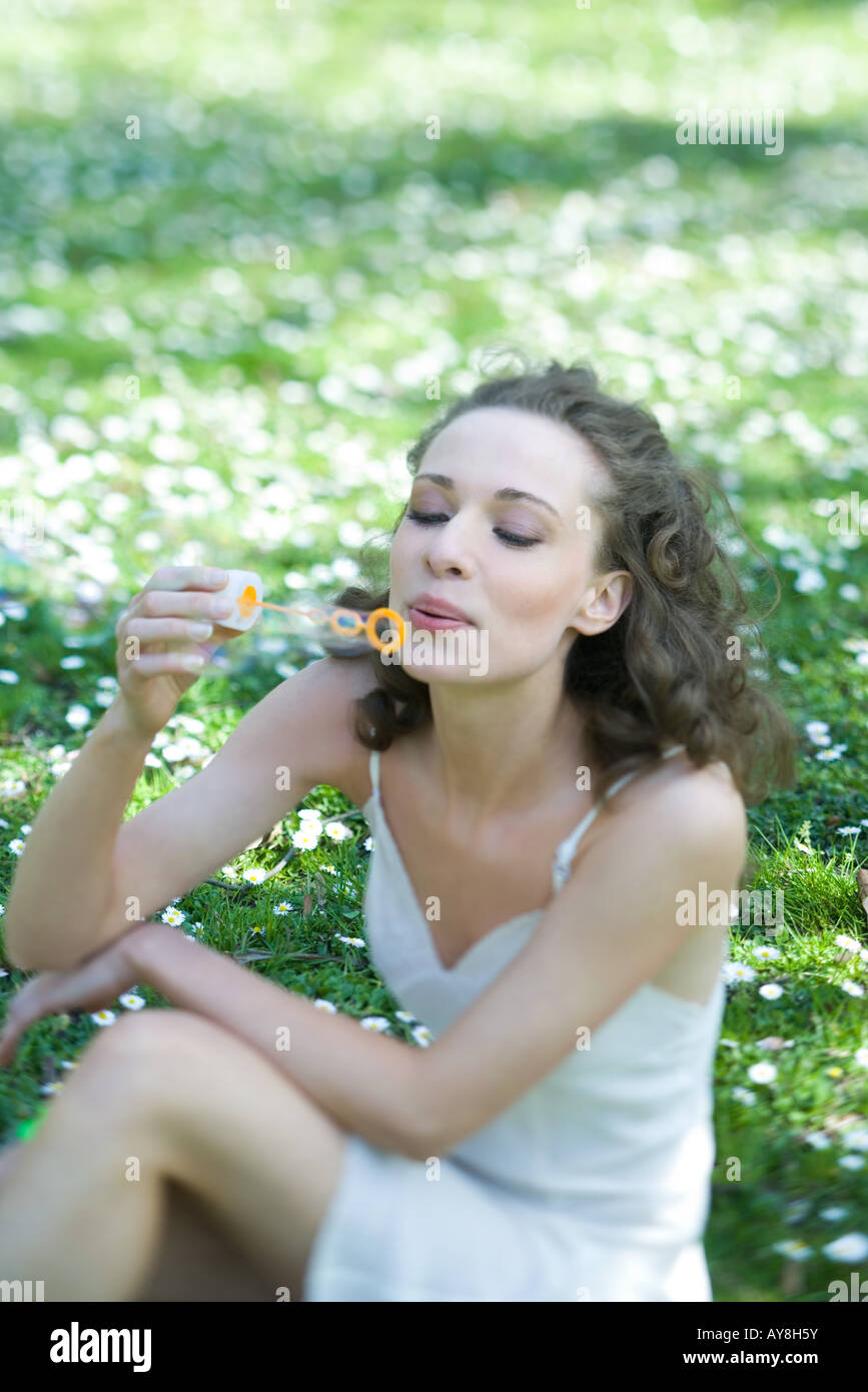 Young woman sitting outdoors, blowing bubbles, looking down - Stock Image