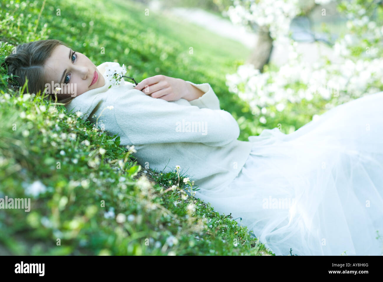 Teenage girl lying on the ground, holding flowers, looking at camera - Stock Image
