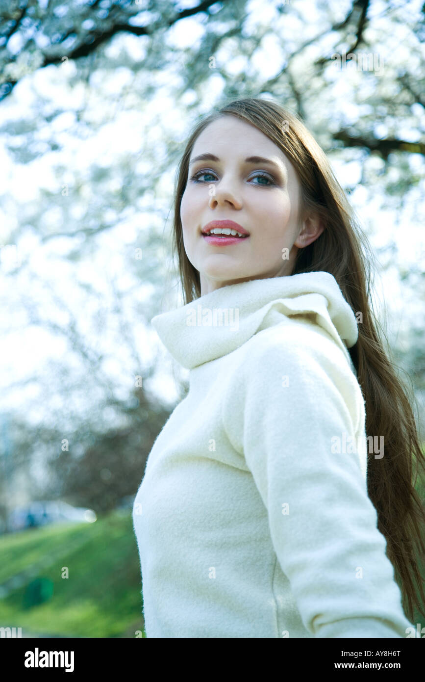 Teenage girl standing outdoors, smiling, low angle view - Stock Image