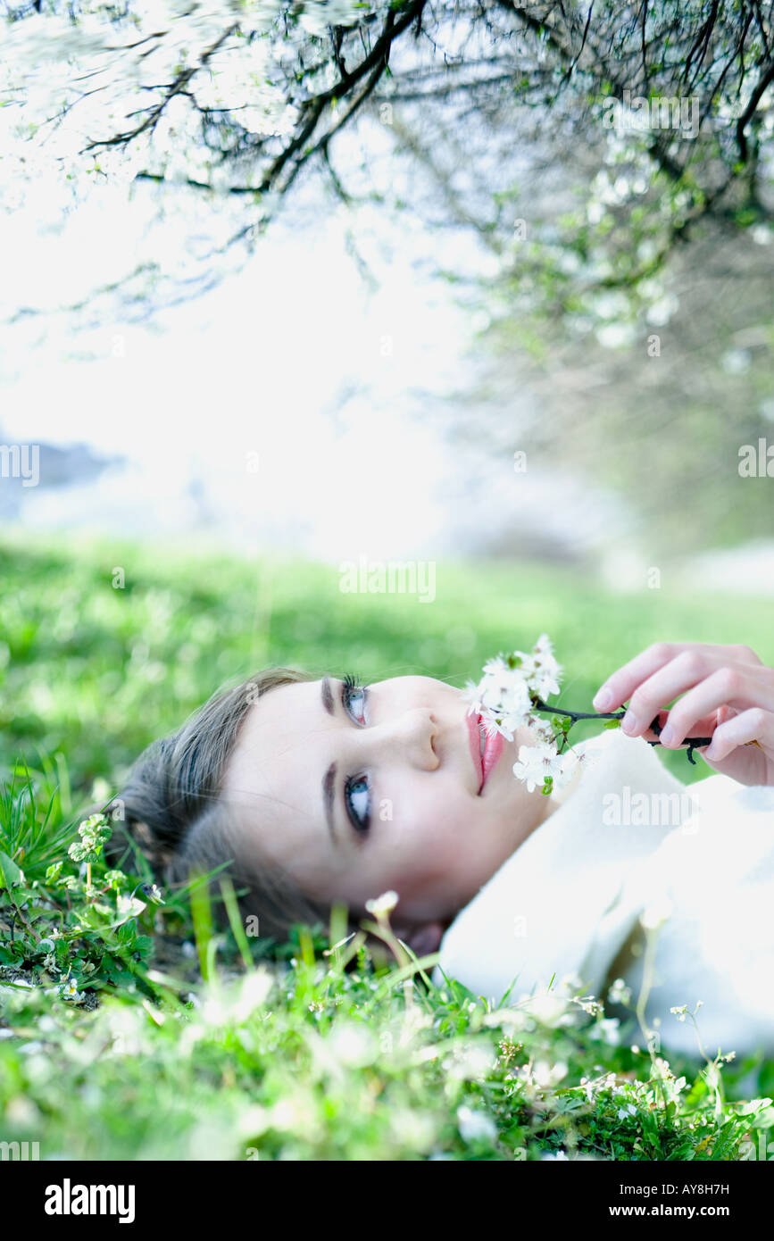 Teenage girl lying on the ground, holding flowers up to face, looking away - Stock Image