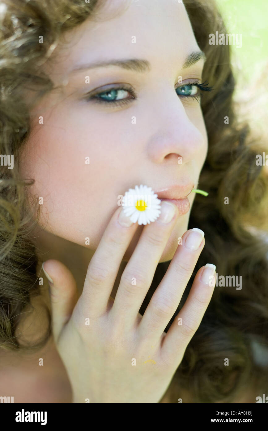 Young woman holding flower in mouth, looking away, close-up - Stock Image