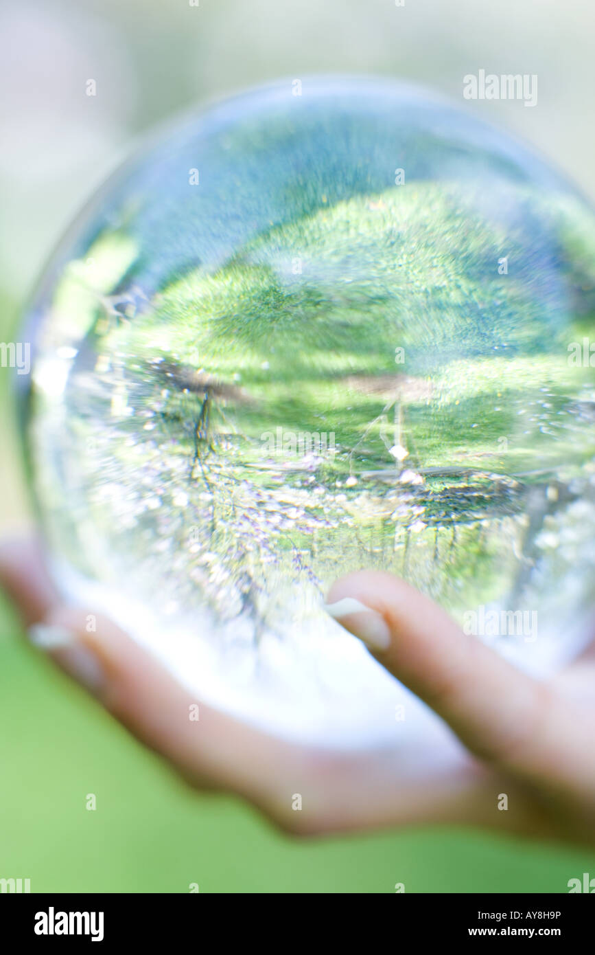 Woman holding glass ball in hand outdoors, extreme close-up - Stock Image