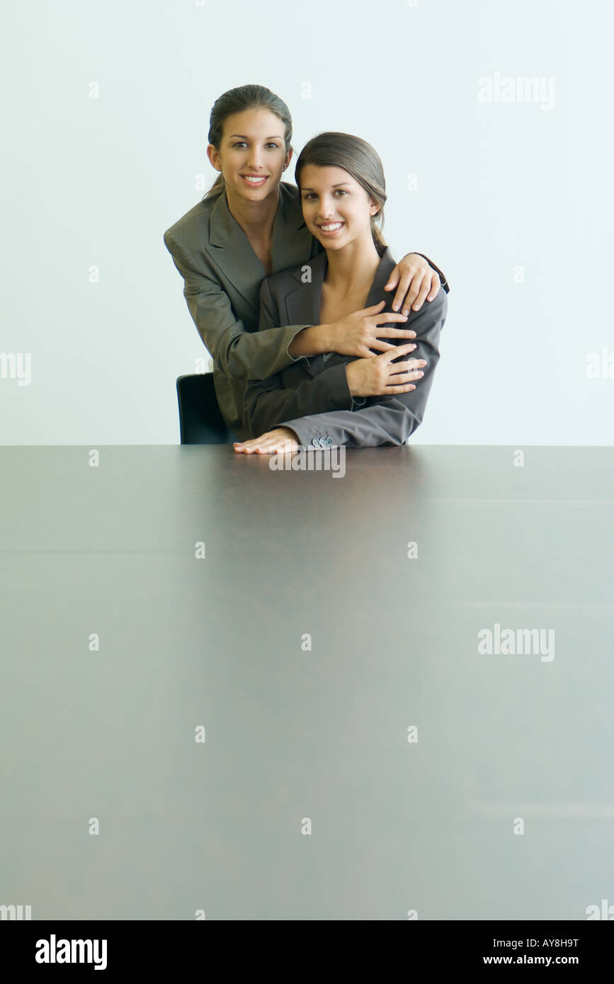 Teenage twin sisters dressed in suits, embracing, smiling at camera together, portrait - Stock Image