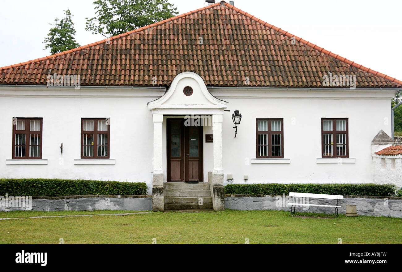 White house with red tile roof windows on either side stock image